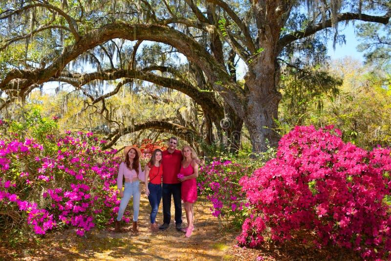 Família feliz de sorriso que aprecia o tempo junto no jardim de florescência bonito em um dia de mola imagens de stock royalty free