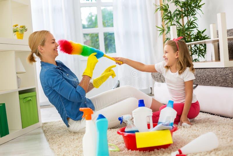 Família feliz de sorriso que joga com ferramenta da limpeza imagem de stock