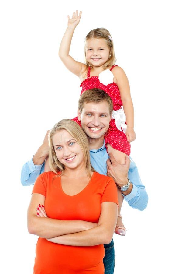 Família feliz de três membros que estão no abraço fotografia de stock
