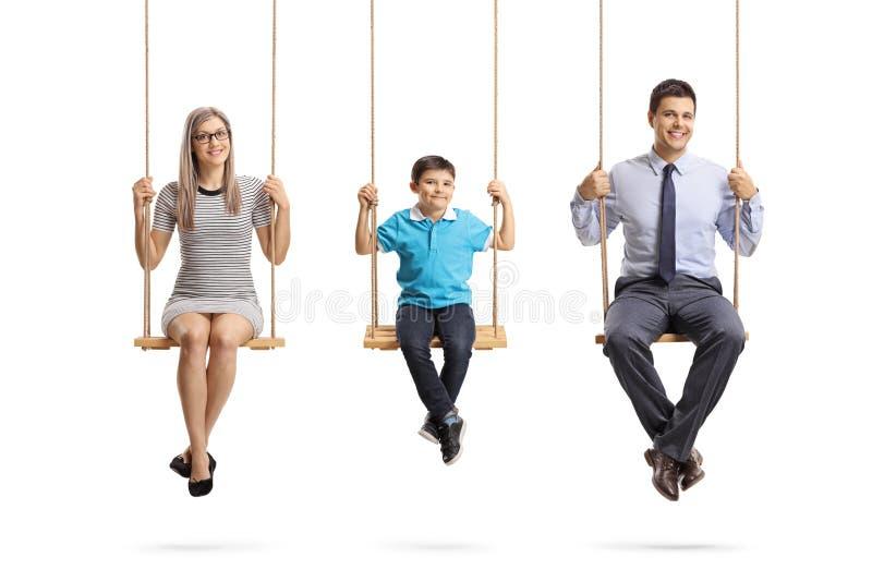 Família feliz de uma mãe, de um pai e de um filho sentando-se em balanços e olhando a câmera imagens de stock