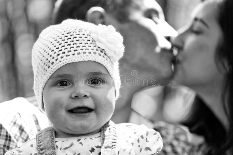 Família feliz desenvolvida Menina e pais do beijo fotos de stock