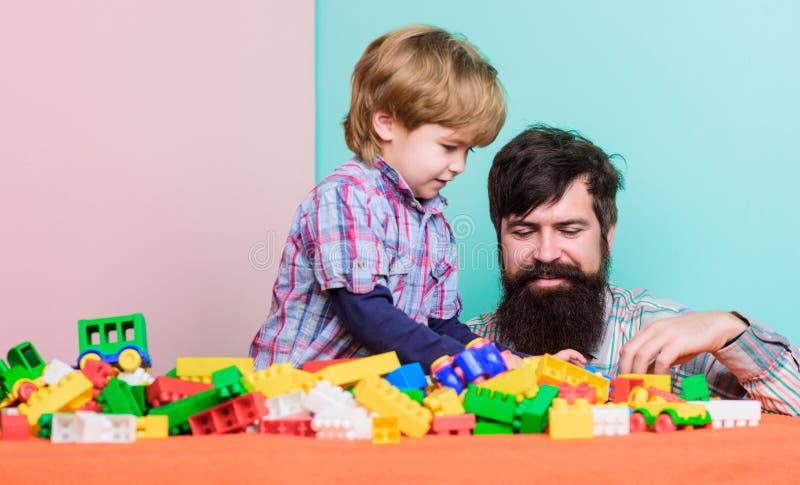 Família feliz Desenvolvimento infantil e educação Importância do jogo junto O paizinho e o filho têm o divertimento Alegre crianç imagem de stock