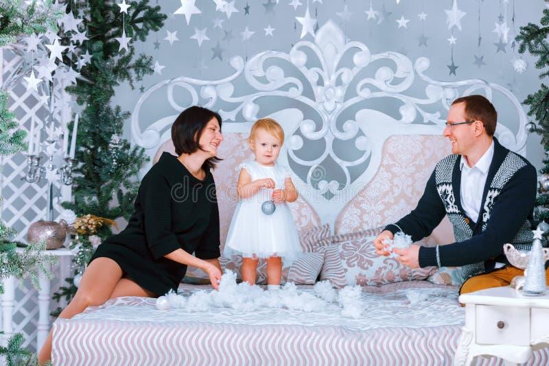Família feliz do Natal das pessoas do três que sentam-se na cama do fundo branco do quarto foto de stock royalty free