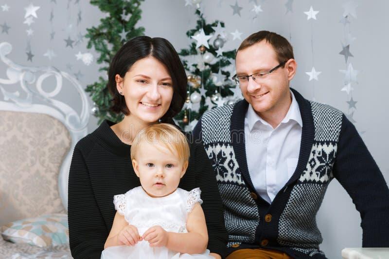 Família feliz do Natal das pessoas do três que sentam-se na cama do fundo branco do quarto fotografia de stock royalty free