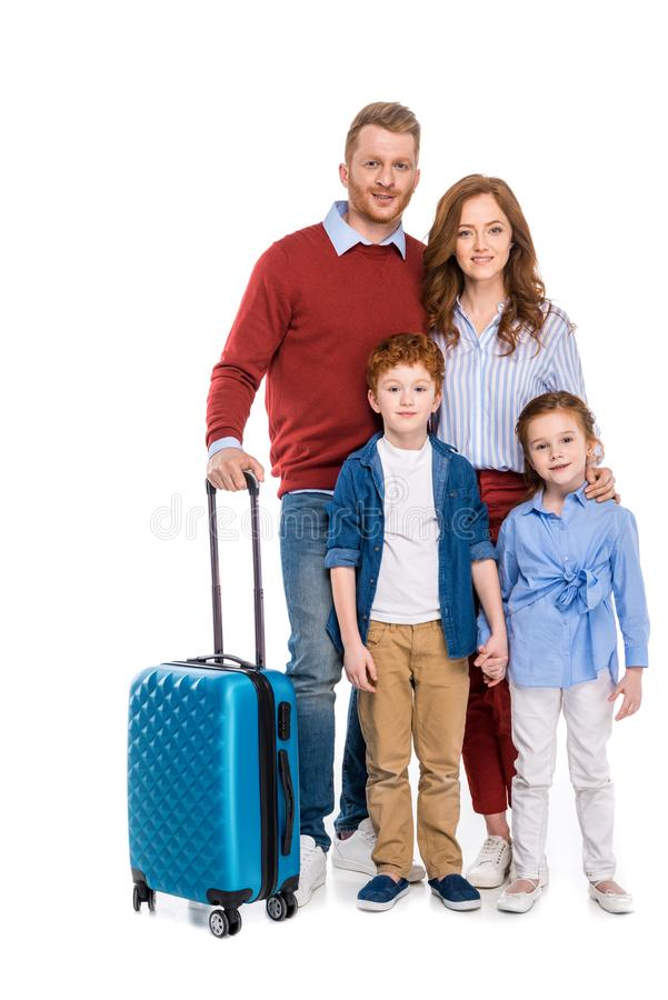família feliz do ruivo com a mala de viagem que está junto e que sorri na câmera imagem de stock