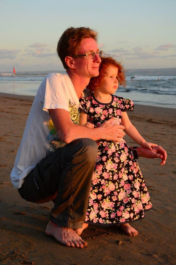 Família feliz do ruivo na praia do por do sol fotografia de stock