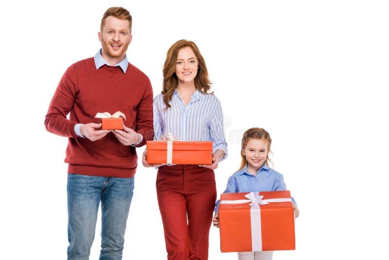 família feliz do ruivo que guarda caixas de presente e que sorri na câmera fotografia de stock