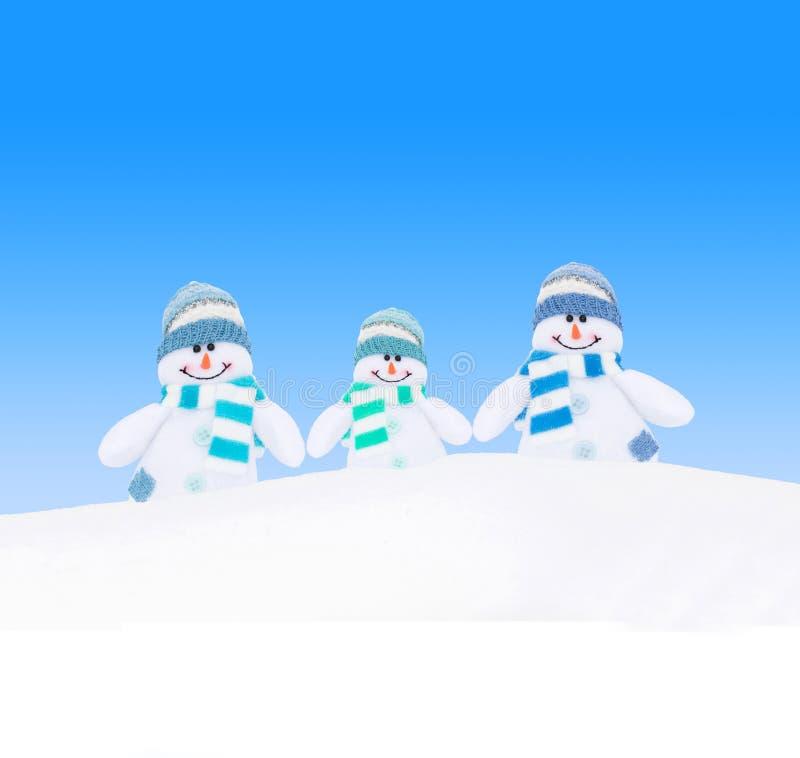 Família feliz dos bonecos de neve do inverno contra o céu azul fotografia de stock