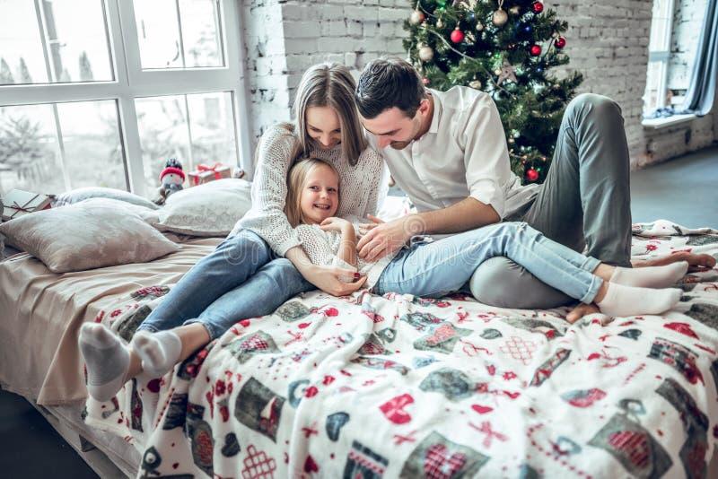 Família feliz em casa Mãe, pai e criança encontrando-se na cama perto da árvore de Natal imagem de stock