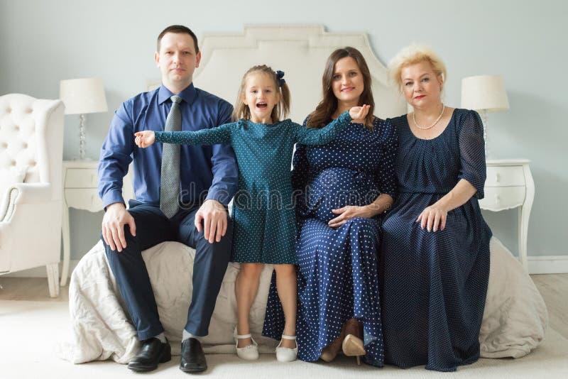 Família feliz em casa Mulher mais idosa, homem, mulher adulta grávida imagem de stock