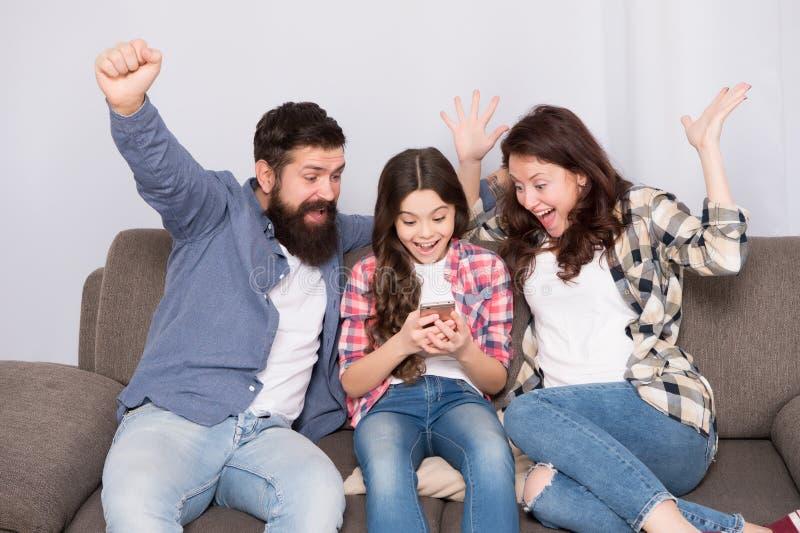 Família feliz em casa Smartphone do uso da menina com mãe e pai Família com humor feliz Família feliz Selfie fotografia de stock royalty free
