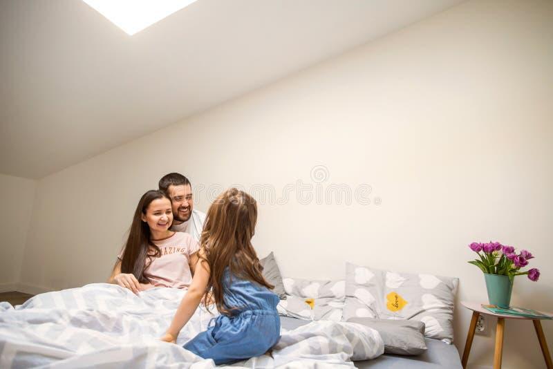 Família feliz em casa em sua sala que comemora o quarto aniversário imagem de stock royalty free