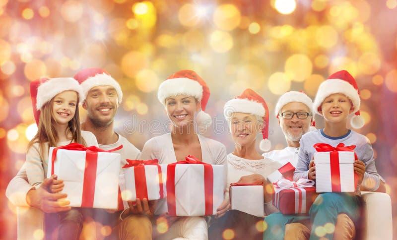 Família feliz em chapéus de Santa com caixas de presente imagens de stock