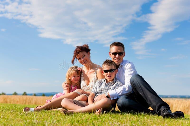 Família feliz em um prado no verão foto de stock