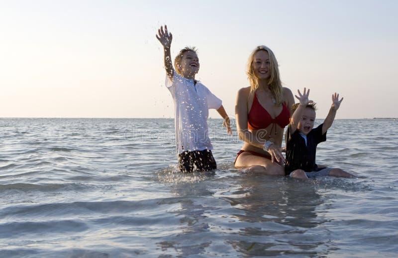 Família feliz em uma praia imagens de stock royalty free