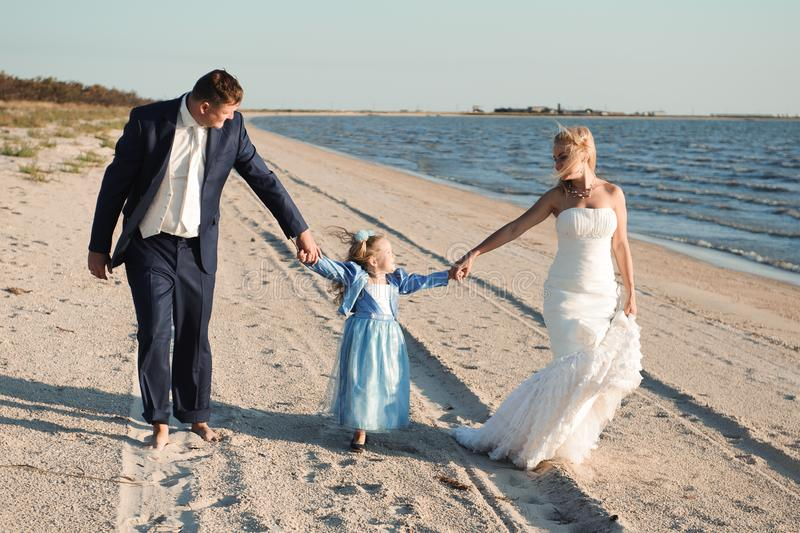 Família feliz em uma praia no nascer do sol - mãe e pai da criança fotografia de stock royalty free