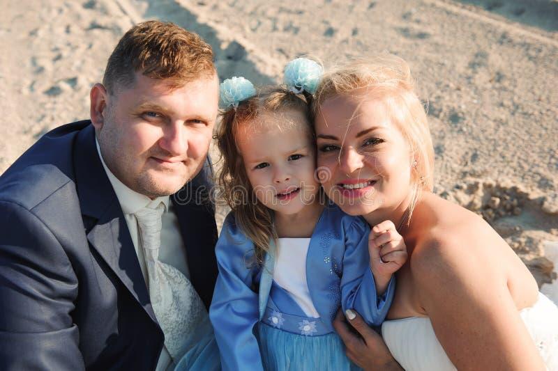 Família feliz em uma praia no nascer do sol - mãe e pai da criança imagem de stock royalty free