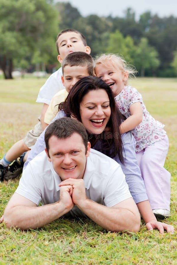Família feliz empilhada acima no parque foto de stock