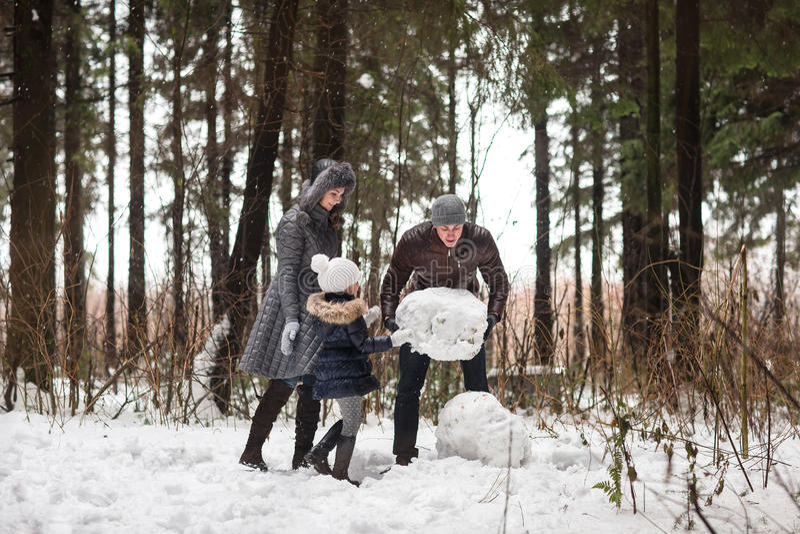 A família feliz esculpe o boneco de neve foto de stock royalty free