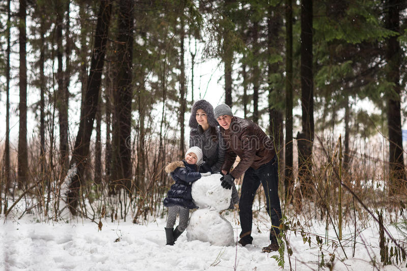 A família feliz esculpe o boneco de neve fotografia de stock