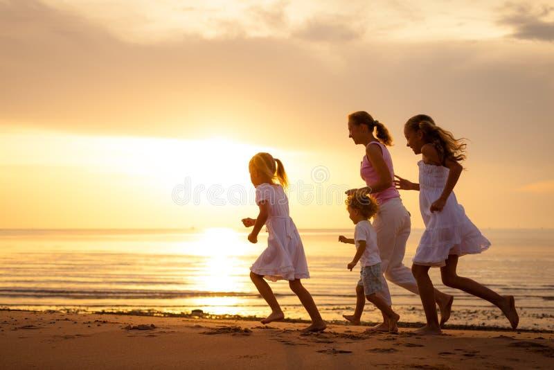 A família feliz está correndo na praia fotos de stock royalty free