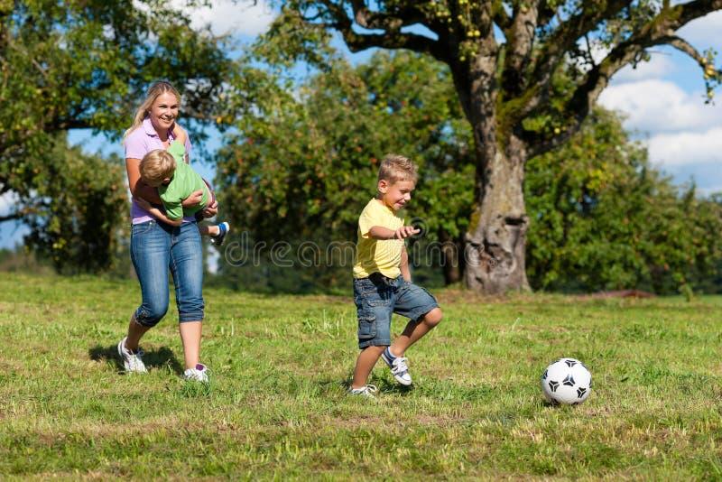 A família feliz está jogando o futebol no verão fotos de stock royalty free