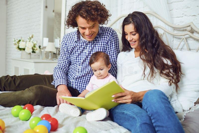 A família feliz está lendo um livro com uma criança na sala imagens de stock