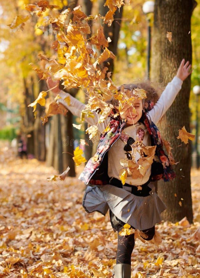 A família feliz está no parque da cidade do outono Runnin das crianças e dos pais foto de stock royalty free