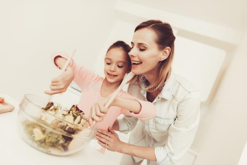 A família feliz está preparando uma salada na cozinha imagens de stock royalty free