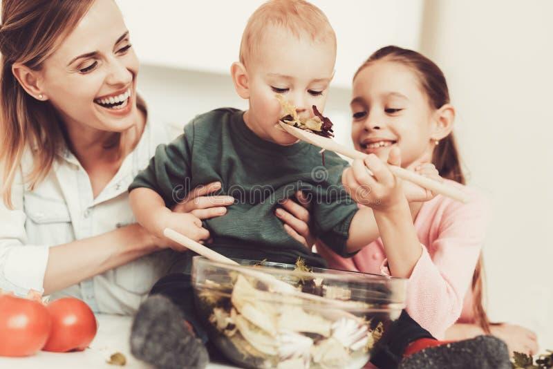A família feliz está preparando uma salada na cozinha foto de stock royalty free