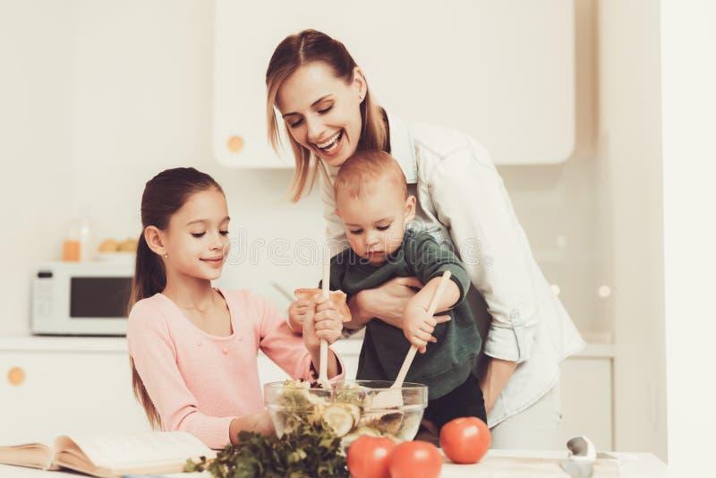 A família feliz está preparando uma salada na cozinha imagem de stock royalty free