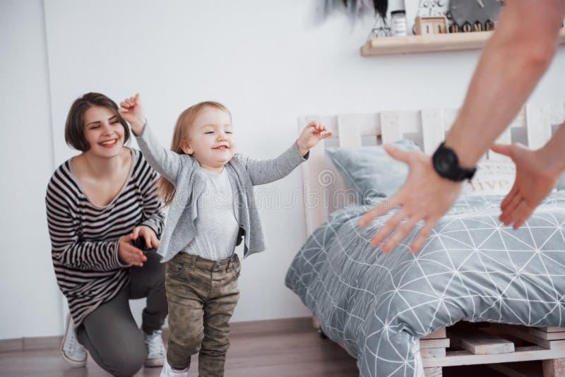 A família feliz está tendo o divertimento em casa A mãe, o pai e a filha pequena com brinquedo do luxuoso estão apreciando sendo  foto de stock