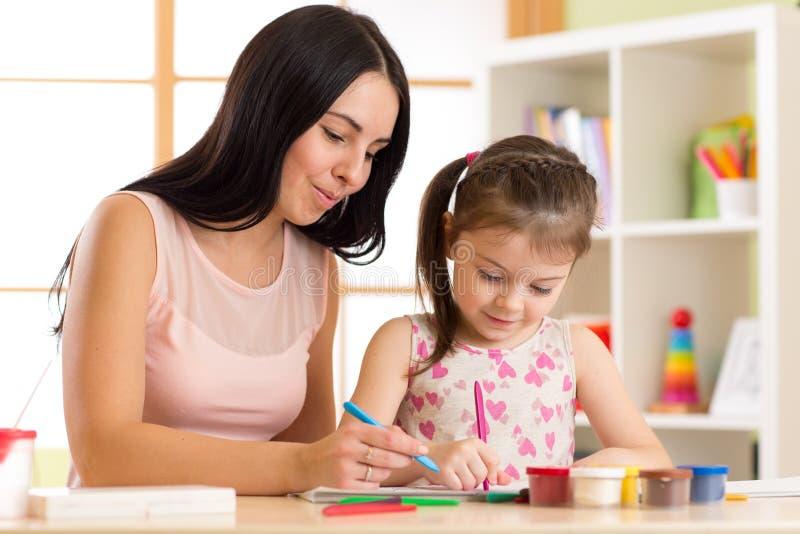 Família feliz A filha da mãe e da criança pinta junto Ajudas da mulher à menina da criança fotos de stock