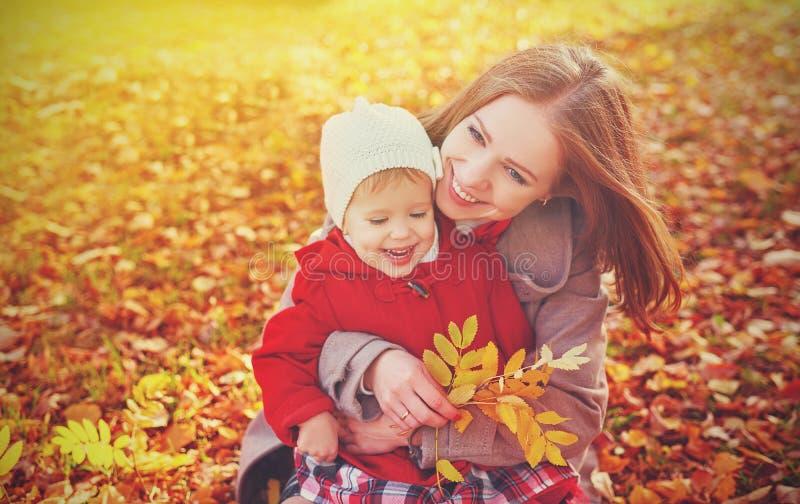 Família feliz: a filha pequena da mãe e da criança joga o afago no outono