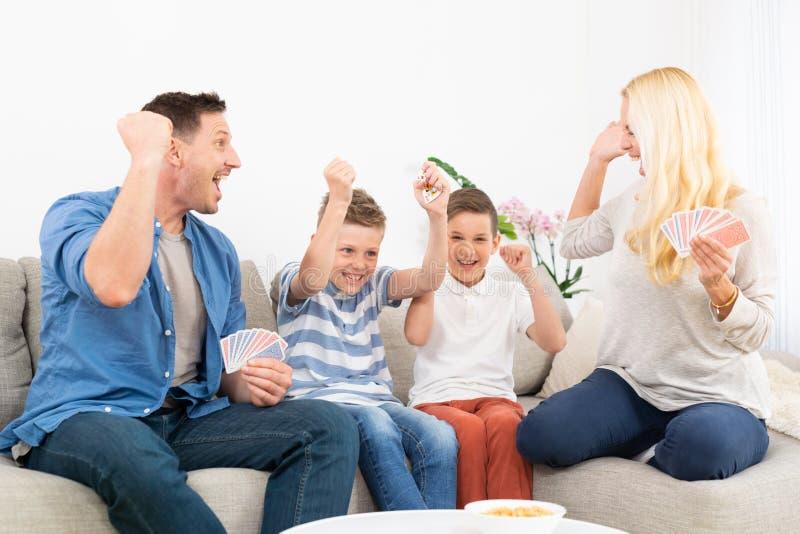 Família feliz jogando cartas no sofá da sala de estar em casa e se divertindo juntos celebrando o vencedor do jogo fotografia de stock
