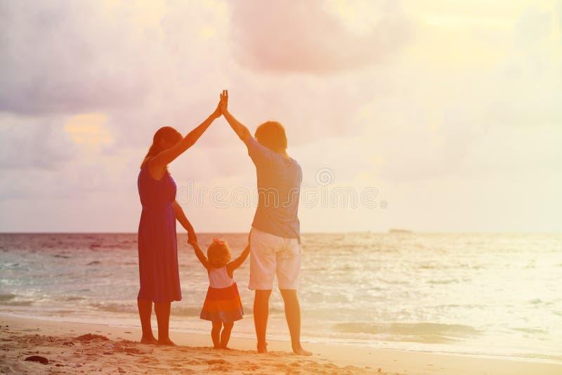 Família feliz junto na praia do por do sol fotos de stock royalty free