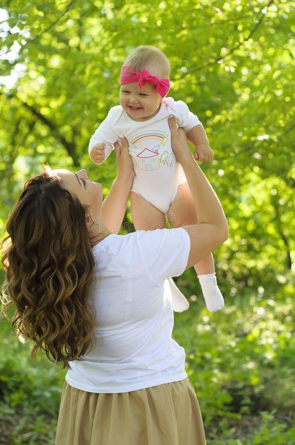Família feliz Mãe com o jogo pequeno da filha no parque imagens de stock royalty free