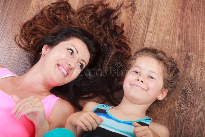 Família feliz Mãe e criança que encontram-se no assoalho home foto de stock