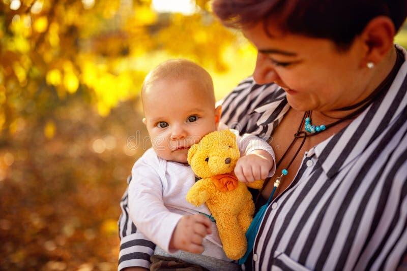 Família feliz - a mãe e o bebê novos no outono estacionam fotografia de stock