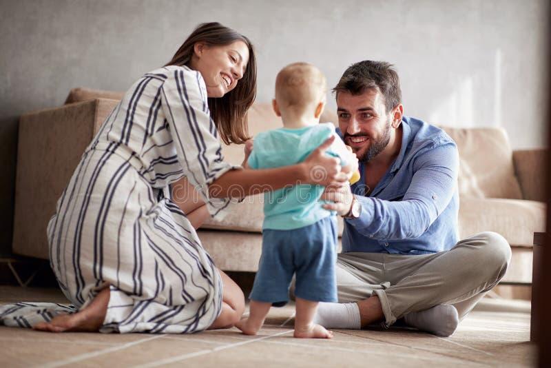 Família feliz - mãe e pai que jogam com um bebê em casa imagens de stock royalty free