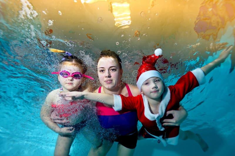 Família feliz - a mãe, a filha e o filho em um terno vermelho Santa Claus nadam debaixo d'água na associação, olhando me e o sorr imagens de stock