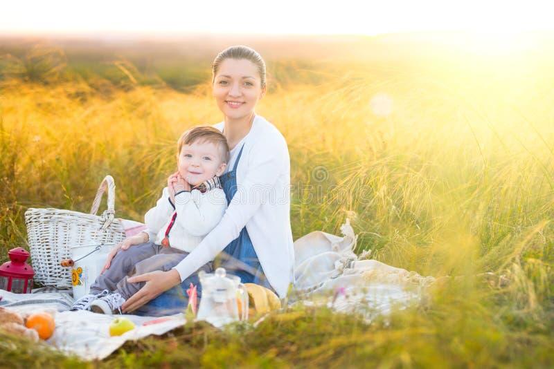 Família feliz Mãe grávida e filho pequeno em um piquenique O conceito do estilo de vida e da infância fotografia de stock
