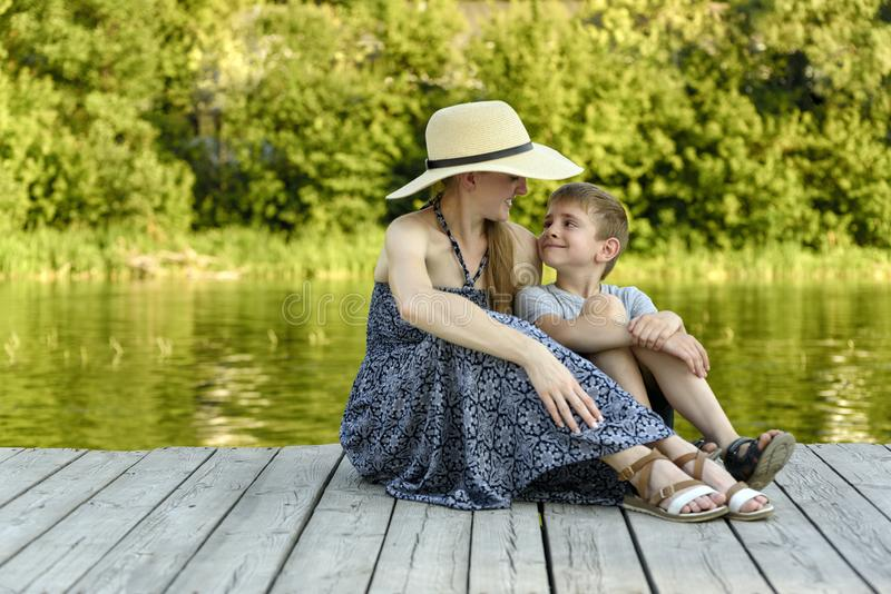 A família feliz, mãe nova com seu filho pequeno está sentando-se no cais pelo rio fotos de stock royalty free