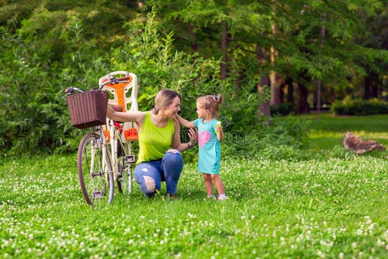 Família feliz Mãe nova e sua filha no parque imagem de stock