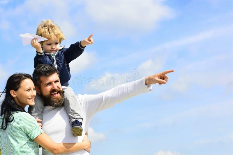 Família feliz - mãe, pai e filho no fundo do céu no verão Pai feliz que dá o passeio do filho para trás no céu no verão imagens de stock