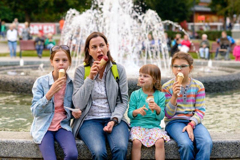 Família feliz - mamã com filhas - que come o gelado fora imagens de stock