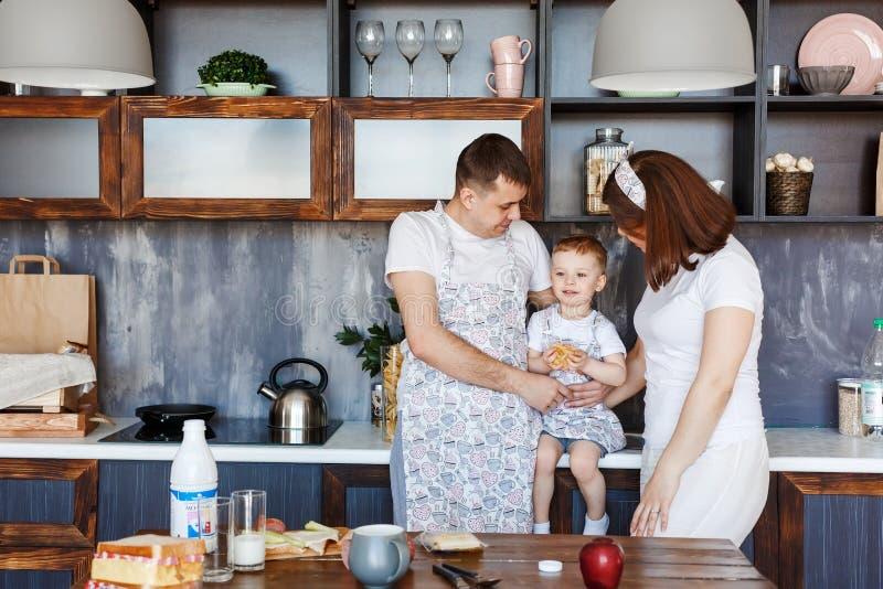 Família feliz - mamã, paizinho e filho na cozinha em casa na manhã fotos de stock royalty free