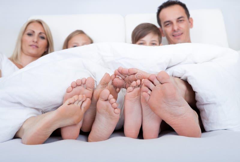 Família feliz na cama sob a tampa que mostra os pés fotografia de stock