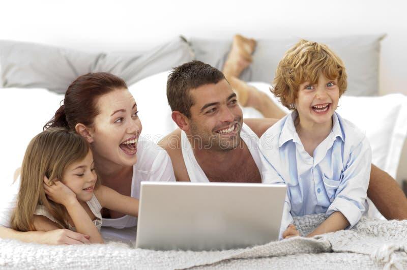Família feliz na cama usando um portátil fotos de stock