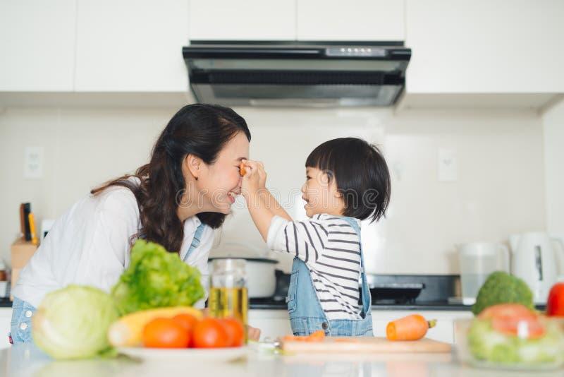 Família feliz na cozinha A filha da mãe e da criança é prepa fotos de stock royalty free